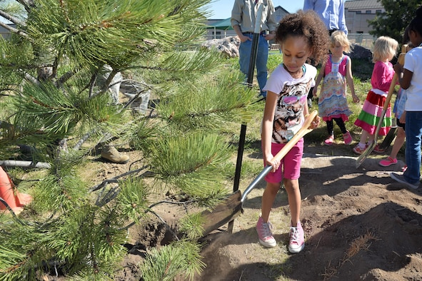 Nylah Council throws dirt at the base of a newly planted tree during the Arbor Day celebration at the Child Development Center at Schriever Air Force Base, Colorado, Friday, June 9, 2017.  Arbor Day promotes tree planting and conservation.  This year, Schriever was recognized for its 19th consecutive year as a Tree City USA recipient. (U.S. Air Force Photo/Dennis Rogers)