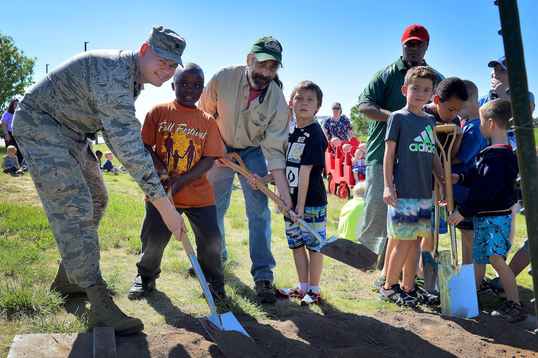 Lt. Col. Andrew DeRosa, 50th Civil Engineer Squadron commander, and Andy Schlosberg, Colorado State Forester, plant a tree with the help of Jahlil Ray and Jordan McCullough at the Child Development Center at Schriever Air Force Base, Colorado, Friday, June 9, 2017.  The tree was planted in honor of Arbor Day, a day to celebrate tree conservation and to recognize Schriever's 19th consecutive year as a Tree City USA recipient.  (U.S. Air Force Photo/Dennis Rogers)