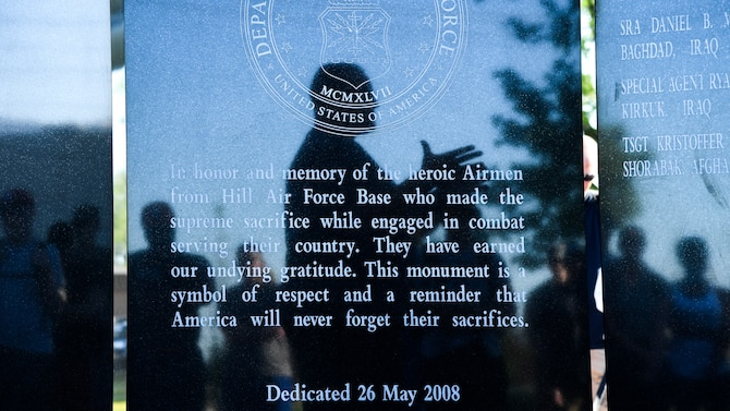 A reflection of Hunter Jones, former AFOSI Detachment 113 commander, appears on a monument to Airmen killed in action at Hill Air Force Base's Memorial Park, June 9. Jones returned to the base to participate in a ruck march honoring SA Ryan Balmer, who was killed in action in Iraq in June 2007. Jones was SA Balmer's commander in 2007. (U.S. Air Force/R. Nial Bradshaw)
