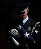 U.S. Air Force Senior Airman Luke Goins, 633d Force Support Squadron ceremonial honor guardsman, inspects the edges of the American Flag, after performing a flag folding ceremony at Joint Base Langley-Eustis, Va., June 12, 2017. It has been more than 100 years since the holiday's inception by President Woodrow Wilson, in 1916. (U.S. Air Force photo/Staff Sgt. Carlin Leslie)
