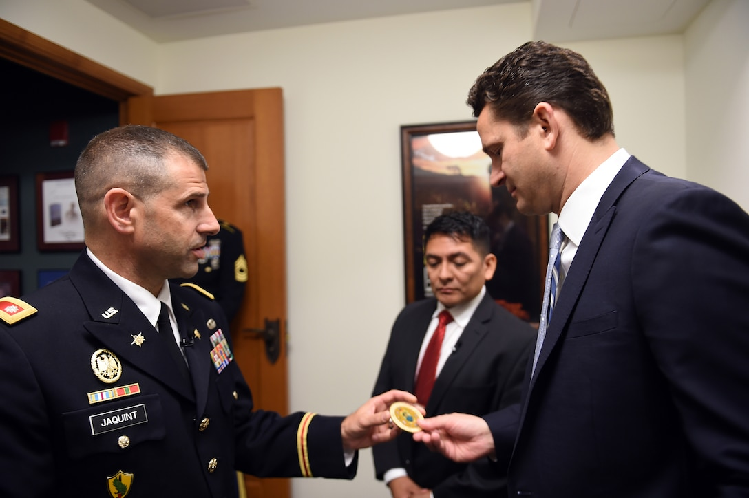 """U.S. Army Reserve Lt. Col. Daniel Jaquint, left, Chief of Staff, 85th Support Command, explains the 85th Support Command's coin to Kenneth Clarke, right, President and Chief Executive Offi-cer, Pritzker Military Museum & Library, at the Pritzker Military Museum & Library in Chicago, June 5, 2017. The coin displays an image of the command's namesake General George Arm-strong Custer in the center on one side and the command's iconic green and red """"CD"""" patch on the reverse side. The coin includes the 85th Support Command's World War II campaign streamers; and the names of the four Soldiers, who were awarded the Medal of Honor during World War II, are etched around the rim of the coin. The 85th Support Command's lineage began as the 85th Infantry Division at Camp Custer, Michigan, where the division was nicknamed the """"Custer Division,"""" on Aug. 5, 1917. The Division was deactivated in 1945 following World War II, then later reactivated in Chicago on February 19, 1947 in the U.S. Army Reserve as a training division. The 85th Spt. Cmd. is celebrating its centennial anniversary this year. (U.S. Army Photo by Sgt. Aaron Berogan/Released)"""