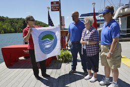 "Diane Parks, chief of operations, U.S. Army Corps of Engineers, Nashville District, presents the ""Clean marina"" flag certifying  ""Clean Marina"" status on Dale Hollow Lake in Burkesville, Ky., to (L to R) Frank, Pat and Patty Brendel for their work in taking the initiative to achieve ""Clean Marina"" status.  The Hendricks Creek Marina on Dale Hollow Lake raised the ""Clean  Marina"" flag today during a dedication ceremony recognizing the marina's voluntary efforts to reduce water pollution and erosion in the Cumberland River watershed, and for promoting environmentally responsible marina and boating practices."