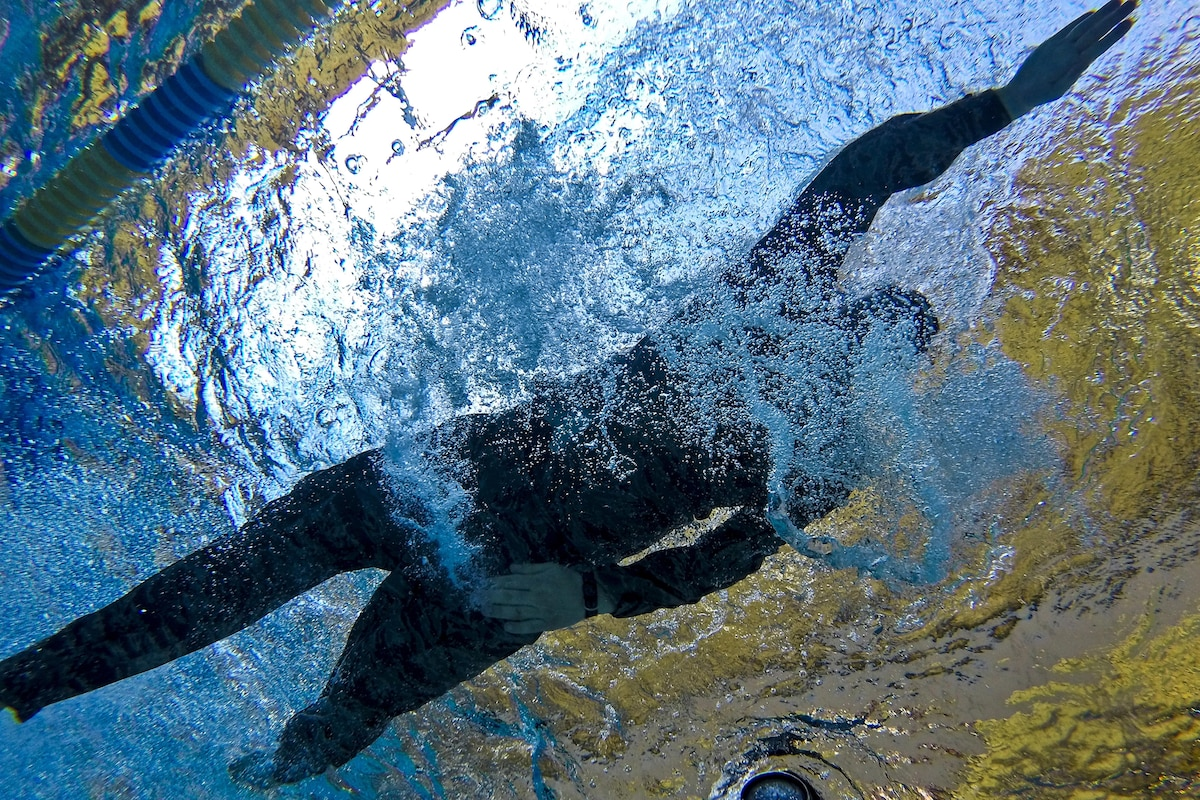 An airman seen from underwater swims a 100-meter challenge.