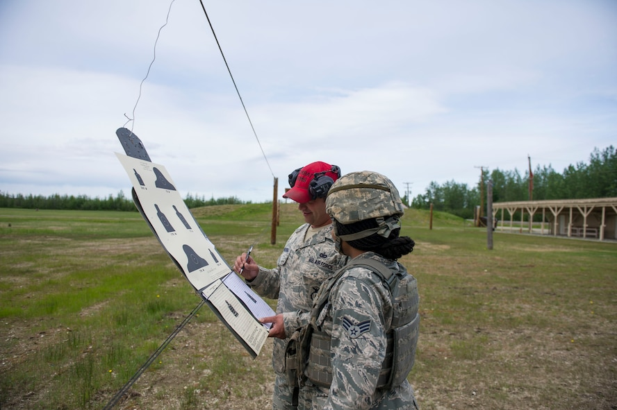 U.S. Air Force Staff Sgt. Gregory Chmielewski, a 354th Security Forces Squadron (SFS) combat arms instructor, helps an SFS Airman site their rifle June 7, 2017, at Eielson Air Force Base, Alaska. Chmielewski and the Combat Arms Training and Maintenance team qualify around 1,100 people every year, and are on schedule to train even more in 2017. (U.S. Air Force photo by Airman 1st Class Isaac Jonson)