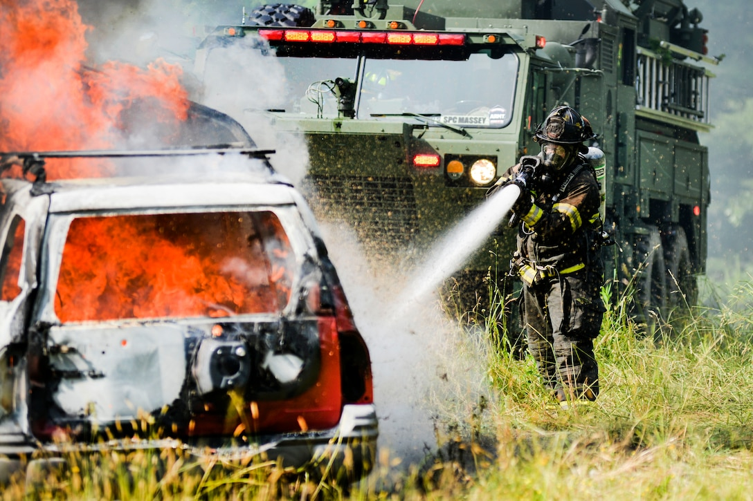 A guardsman extinguishes a fire at a simulated crash site during an exercise.