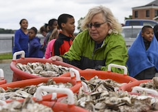 Betsy McAllister, Hampton City Schools science teacher specialist, prepares for an oyster planting event at Joint Base Langley-Eustis, Va., June 8, 2017. As generations of oysters settle on top of each other and grow, they form reefs that provide structured habitat for many species of fish and crabs. (U.S. Air Force photo/Airman 1st Class Anthony Nin Leclerec)
