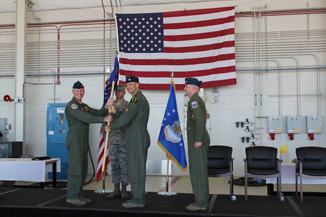 388th Fighter Wing Operations Group commander Col. Jason Rueschhoff hands the 4th Fighter Squadron guidon to new 4th Fighter Squadron commander Lt. Col. Yosef Morris at a ceremony June 9 at Hill Air Force Base as former commander Lt. Col. Steven Engberg stands at attention.