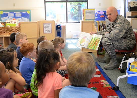"""Col. Roman L. Hund (left), installation commander, reads """"Mister Seahorse"""" by Eric Carle to children at the Child Development Center June 12. Hund was invited to read to children by CDC officials. (U.S. Air Force photo by Linda LaBonte Britt)"""