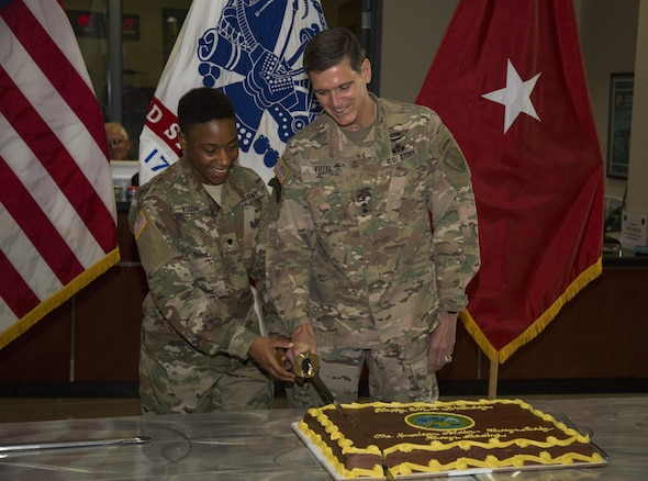 U.S. Army Gen Joseph Votel, commander U.S. Central Command, and Army Specialist Chelsey Woods, representing the oldest and youngest soldier, cut into a cake with a ceremonial sword. USCENTCOM HQ's Army element celebrated the U.S. Army's 242nd birthday with a cake cutting ceremony. (Photo by Tom Gagnier)
