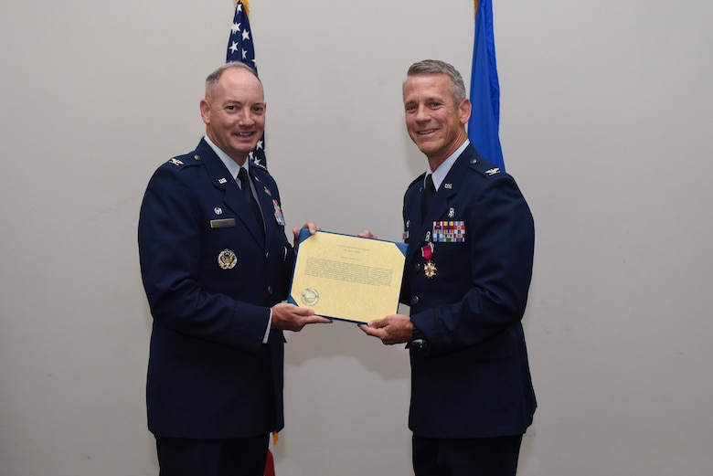 U.S. Air Force Col. Michael Downs, 17th Training Wing Commander, presents a Meritorious Service certificate to Col. Steven Van De Walle, 17th Medical Group Commander, at the Event Center on Goodfellow Air Force Base, Texas, June 13, 2017. The event honored Van De Walle's service to his unit and welcomed its new commander Col. Janet Urbanski. (U.S. Air Force photo by Airman 1st Class Chase Sousa/Released)