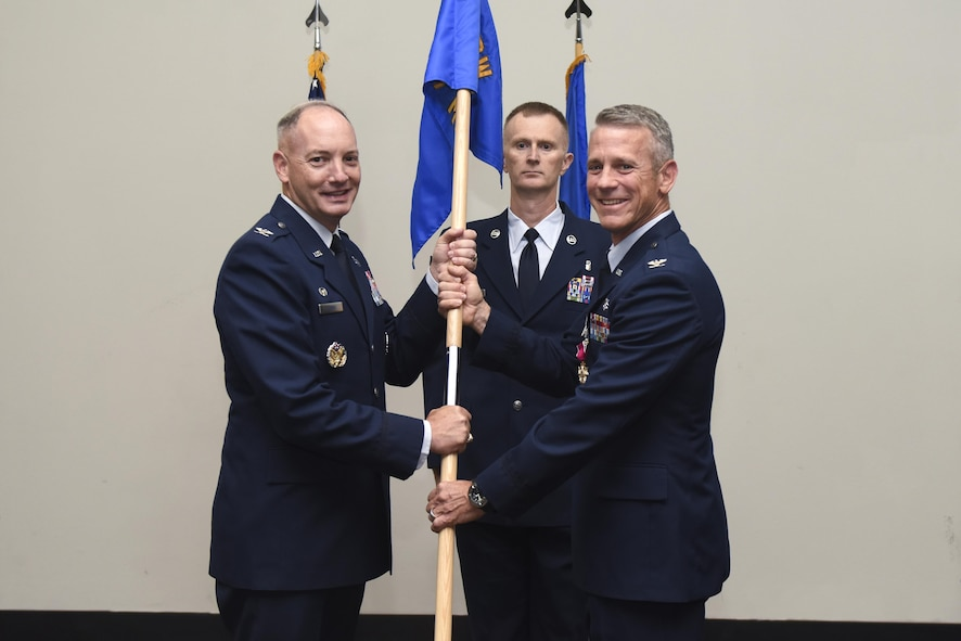U.S. Air Force Col. Steven Van De Walle, 17th Medical Group Commander, passes the unit guideon to Col. Michael Downs, 17th Training Wing Commander, during the 17th MDG Change of Command ceremony at the Event Center on Goodfellow Air Force Base, Texas, June 13, 2017. The event honored Van De Walle's service to his unit and welcomed its new commander Col. Janet Urbanski. (U.S. Air Force photo by Airman 1st Class Chase Sousa/Released)