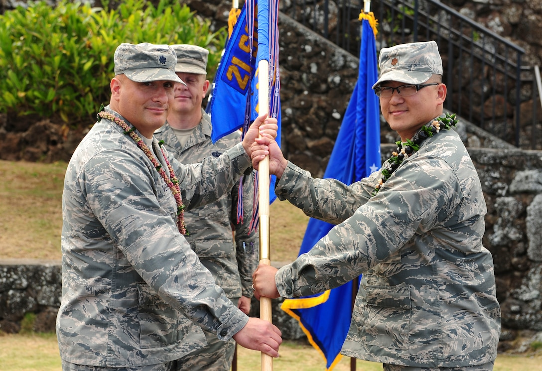 Lt. Col. Phillip Verroco, 21st Space Operations Squadron commander, gives the detachment flag to Maj. Edmond Chan, Detachment 3 incoming commander, during the Detachment 3 Change of Command Ceremony, Kaena Point, Hawaii, June 9, 2017.  Detachment 3 is a component of the 21st Space Operations Squadron, 50th Network Operations Group, 50th Space Wing, and is located on the western tip of Oahu.  It is the oldest and one of seven worldwide remote tracking stations in the Air Force Satellite Control Network.  (U.S. Air Force photo by Tech. Sgt. Heather Redman)