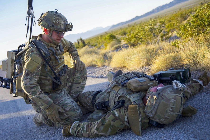 Senior Airman William Butler, 99th Civil Engineer Squadron explosive ordnance disposal technician, simulates tactical combat casualty care with Staff Sgt. Myles Corbin, 99 CES EOD technician, who suffered a lower limb wound at the Nevada Test and Training Range June 7, 2017. Tactical combat casualty care provides immediate aide in hazardous situations. (U.S. Air Force photo by Airman 1st Class Andrew D. Sarver/Released)
