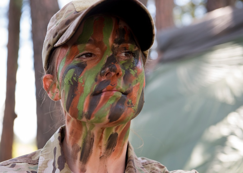 Senior Airman Brittany Wilson, 22nd Training Group survival specialist, displays face paint camouflage Apr. 28, 2017, at Fairchild Air Force Base, Washington. Avoiding detection and moving while camouflaged is a critical part of the evasion portion of survival training. (U.S. Air Force Photo / Airman 1st Class Ryan Lackey)