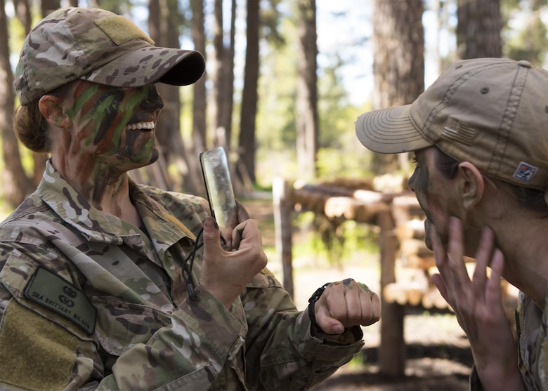 Senior Airman Brittany Wilson and Staff Sgt. Bethany Bowater, 22nd Training Squadron survival instructors, help each other apply face paints during a camouflage demonstration Apr. 28, Fairchild Air Force Base, Washington. Survival specialists undergo intense training to qualify as instructors, as they must display excellence in any task they may ask of their students. (U.S. Air Force Photo / Airman 1st Class Ryan Lackey)
