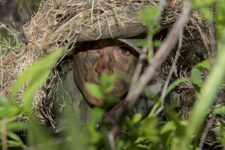 Staff Sgt. Bethany Bowater, 22nd Training Squadron survival specalist, peeks out from under the ground foilage Apr. 28, Fairchild Air Force Base, Washington. Survival students undergo a challenge to move 200 meteres undetected by a watch tower. (U.S. Air Force Photo / Airman 1st Class Ryan Lackey)
