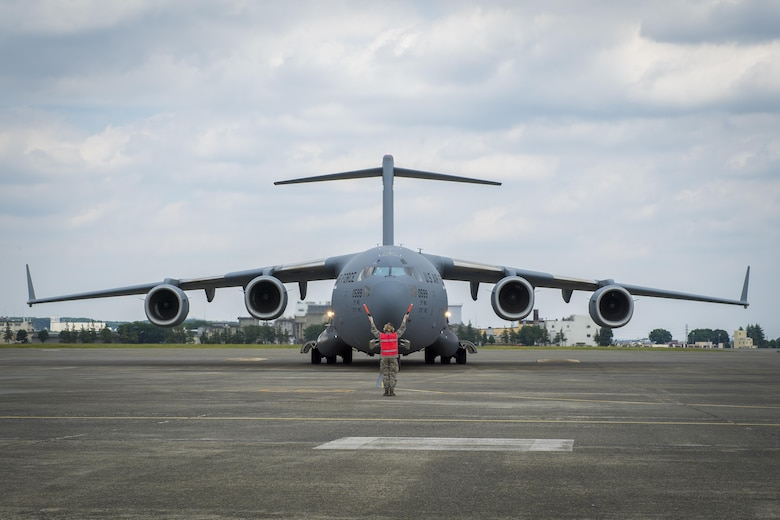 A C-17 Globe Master is marshaled to a parking spot, June 6, 2017, at Yokota Air Base, Japan. The C-17 is part of the Noncombatant Evacuation Operations exercise, Focused Passage 2017, designed to exercise NEO procedures for an evacuation of U.S. citizens from the Republic of Korea. (U.S. Air Force photo by Airman 1st Class Donald Hudson)