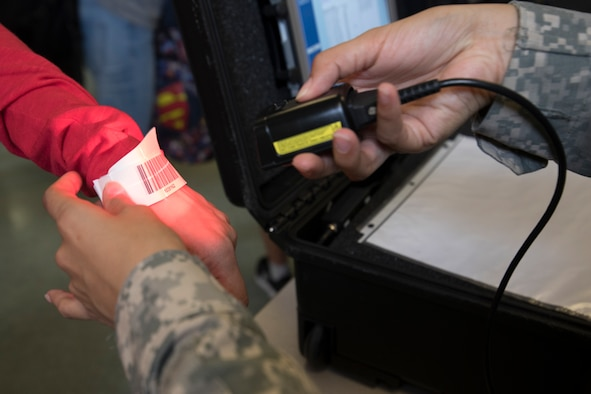U.S. Army Specialist Brianna Doo, U.S. Army in Japan band, scans a bracelet with a tracking system barcode at Yokota Air Base, Japan, during noncombatant evacuation exercise Focused Passage 2017, June 6, 2017. Over 360 active duty, family members and simulated pets participated in the exercise. (U.S. Air Force photo/Yasuo Osakabe)