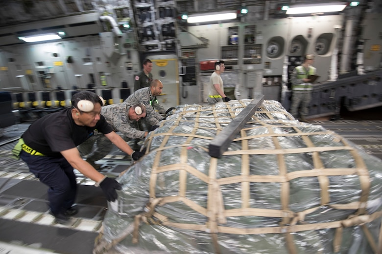 Members with the 730th Air Mobility Squadron unload a bundle from a C-17 Globemaster III at Yokota Air Base, Japan, June 6, 2017, during exercise Focused Passage 2017. FP 2017 is designed to exercise the command's Noncombatant Evacuation Operations procedures for an evacuation from the Republic of Korea. (U.S. Air Force photo by Yasuo Osakabe)