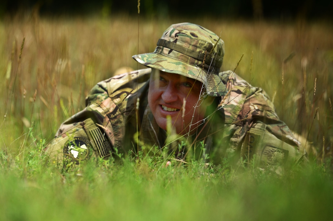 U.S. Air Force Tech. Sgt. James Binari, 7th Weather Squadron Detachment 4 NCO in charge of mission integration function, performs a concealment exercise at the Mainz Sand Dunes, Germany, June 13, 2017. While administratively part of the Air Force, Army weather support Airmen are embedded with the U.S. Army and certify in a number of Soldier tasks. (U.S. Air Force photo by Airman 1st Class Joshua Magbanua))