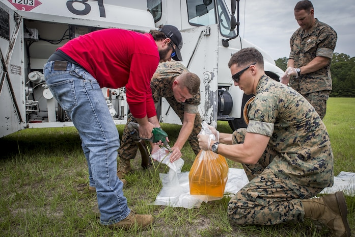 Marines  and  a  fuels  technician  fill  four-gallon  bags  with  fuel  to  conduct  a  demolition  exercise at the Explosive Ordnance Range aboard Marine Corps Air Station Beaufort, June 1. The MCAS Beaufort EOD Marines conducted the demolition exercise to detonate unused explosives from the 2017 MCAS Beaufort Air Show using the opportunity to practice for future air shows. The fuel bags were ignited to create the 'wall of fire', a pyrotechnic display used during air shows. The Marines are EOD technicians with EOD, MCAS Beaufort and the fuels technician is with Marine Wing Support Detachment 31, Marine Aircraft Group 31.