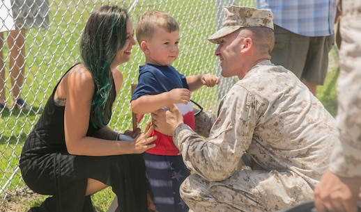 Sgt. Christopher Toy, squad leader, 4th Platoon, Company C., Fleet Anti-terrorism Security Team, U.S. Marine Corps Security Force Regiment, is greeted by his wife and son upon his return  to Camp Allen, Norfolk, Va., June 12, after a six-month deployment to Bahrain. During the deployment, Marines from 4th platoon reinforced embassies in Kuwait and Oman, participated in Operation Eager Lion in Jordan, and set up defensive plans for Bahrain Marine Corps and Bahrain National Guard, to list a few. (U.S. Marine Corps photo by Sgt. Kayla D. Rivera/Released)
