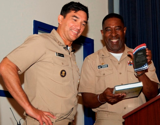 "DAHLGREN, Va. - Capt. Godfrey ""Gus"" Weekes, Naval Surface Warfare Center Dahlgren Division (NSWCDD) commanding officer, presents the Dahlgren history book, ""The Sound of Freedom,"" and a plaque to Rear Adm. Patrick Piercey, Naval Surface Force Atlantic commander, at the NSWCDD sponsored Asian American and Pacific Islander Heritage Month Observance, May 23. ""We are united by our love of freedom and love of the values that we have as Americans despite what source you came in to become an American,"" said Piercey. ""We are celebrating diversity without being divisive and recognizing that we are truly stronger because of our diversity."""
