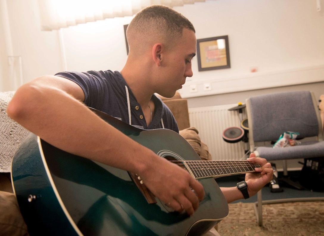 An Airman practices guitar in the music room at Club 7 on Ramstein Air Base, June 10, 2017. The Ramstein and Kapaun Air Station Club 7s have a number of facilities including music rooms, game rooms and movie rooms for junior enlisted Airmen to enjoy. (U.S. Air Force photo by Senior Airman Elizabeth Baker)