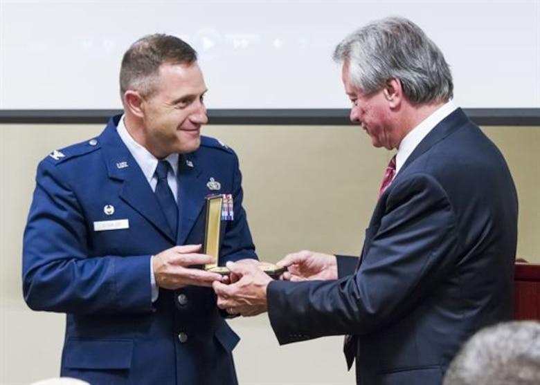 Col. Kirk B. Stabler, the Air Force Office of Special Investigations commander, presents fallen Special Agent Lee Hitchcock's Bronze Star Medal  to his brother, Craig Hitchcock, during the OSI headquarters inaugural Celebration of Life Remembrance Ceremony May 22, 2017, at Quantico, Va. (U.S. Air Force photo/Michael Hastings)