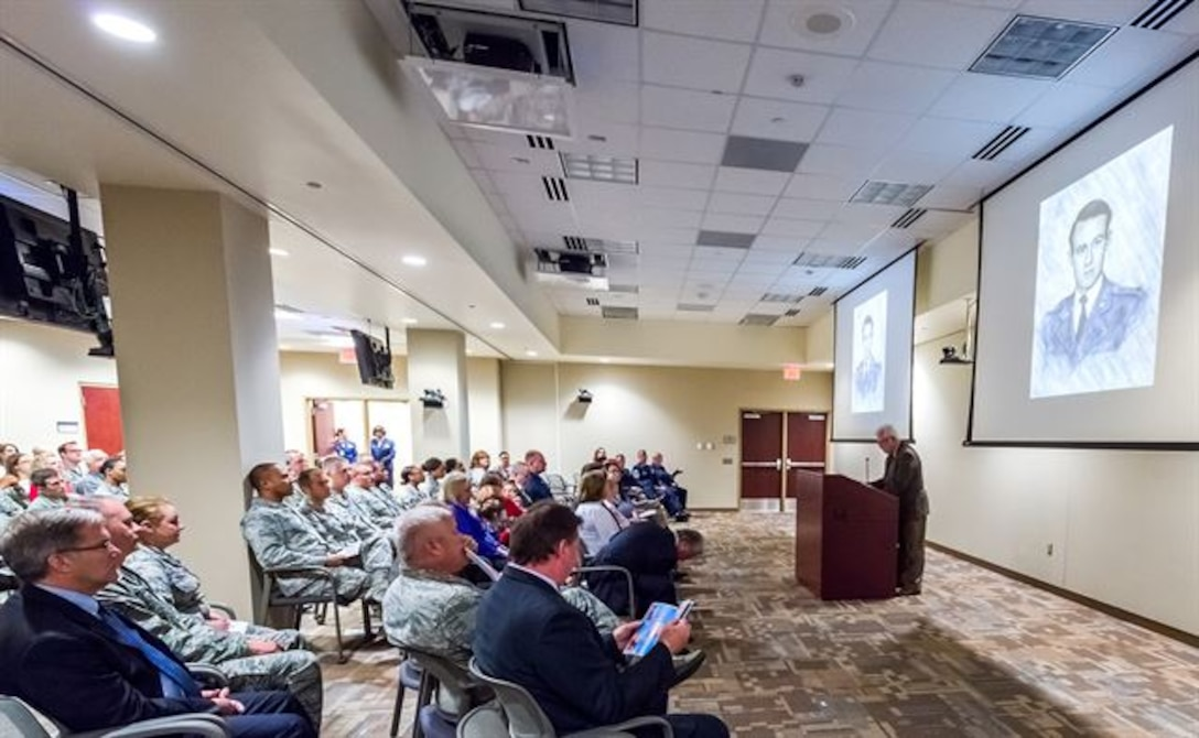 The portrait of the first Air Force Office of Special Investigations fallen Special Agent, Lee Hitchcock, is shown on two large screens during the OSI headquarters inaugural Celebration of Life Remembrance Ceremony May 22, 2017, at Quantico, Va. (U.S. Air Force photo/Michael Hastings)