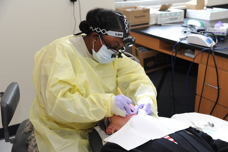 Air National Guard Tech. Sgt. Charissa Younce, dental technician, 125th Fighter Wing, Jacksonville, Florida, cleans Gayla Terdening teeth. Terdening participated in the no-cost medical services offered during the Ozark Highlands Innovated Readiness Training, Mountain Home, Arkansas, 5-12 June. (U.S. Air Force photo by Tech. Sgt. Peter Dean)