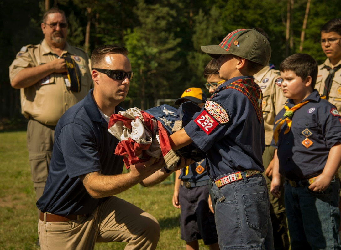 A Cub Scouts of America leader takes a U.S. flag from a Cub Scout to lay on a fire during a Flag Day flag disposal ceremony on Ramstein Air Base, Germany, June 14, 2017. Ramstein personnel who are members of the Veterans of Foreign Wars of the U.S., American Legion, Kaiserslautern Military Community Center Masonic Organizations, and Boy Scouts of America joined to lay U.S. flags to rest during a Flag Day flag disposal ceremony, marking the first time these four organizations had conducted such a ceremony on Ramstein in four years. (U.S. Air Force photo by Senior Airman Elizabeth Baker.)