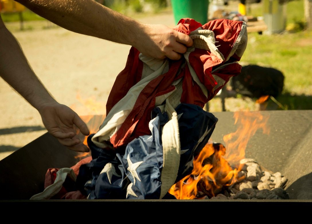 """A Cub Scouts of America leader respectfully disposes of a U.S. flag during a Flag Day flag disposal ceremony on Ramstein Air Base, Germany, June 14, 2017. The ceremony was conducted in accordance with the United States Flag Code which states: """"The Flag, when it is in such condition that it is no longer a fitting emblem of display, should be destroyed in a dignified way, preferably by burning."""" (U.S. Air Force photo by Senior Airman Elizabeth Baker.)"""
