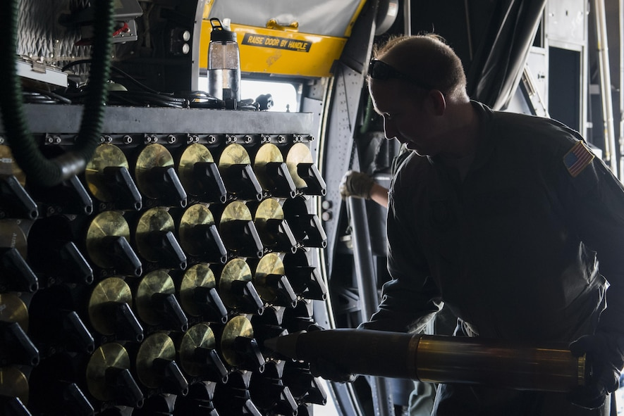 Tech. Sgt. William Sell, 551st Special Operations Squadron aerial gunner evaluator, loads a 105mm round into an ammunition rack aboard an AC-130W Stinger II gunship at Cannon Air Force Base, New Mexico, June 13, 2017. Before loading the round into the ammo rack, Sell performs a quick inspection to ensure it's not damaged in any way. (U.S. Air Force photo by Staff Sgt. Michael Washburn/Released)