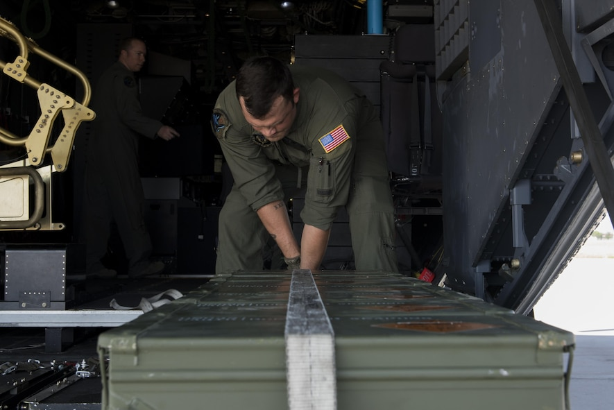 Senior Airman Justin Bird, 551st Special Operations Squadron aerial gunner, straps down 30mm ammunition containers aboard an AC-130W Stinger II at Cannon Air Force Base, New Mexico, June 13, 2017. The objective for the mission was live-fire training as well as an opportunity to train students. (U.S. Air Force photo by Staff Sgt. Michael Washburn/Released)