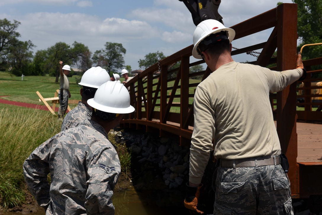 Twenty-second Civil Engineer Squadron Airmen redirect a bridge June 14, 2017 at the Kruger Recreational 2-mile track at McConnell Air Force Base, Kan. The 22nd CES replaced an older bridge that fell into the creek located on the track. (U.S. Air Force photo/Airman 1st Class Alan Ricker)