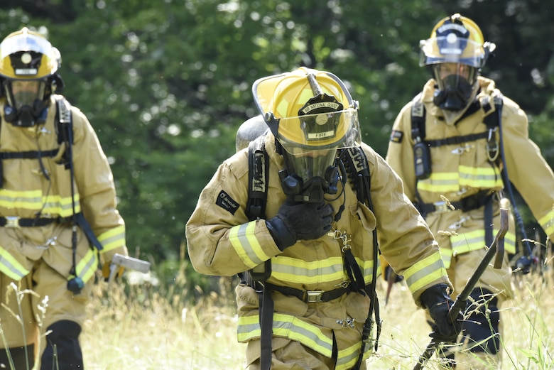 Three fire fighters with the North Carolina Nation Guard's Army and Air Force firefighting team walk away from the site of a simulated fire while at Vigilant Catamount, an interagency domestic exercise between local, state, and military personnel in North Carolina, at Dupont State Forest, Hendersonville North Carolina, June 8, 2017. Vigilant Catamount is a multi-day exercise testing emergency response, starting with the simulated crash of an F-15 aircraft. The fire fighters helped to extinguish two burning vehicles set ablaze to test military emergency firefighting capabilities.