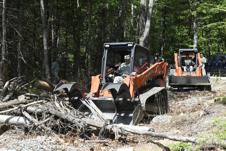 U.S. Air Force Staff Sgt. Adam Palmer (left) and Staff Sgt. Alan L. Zimmerman (right) heavy equipment operators with the 145th Airlift Wing Civil Engineer Squadron operate skid loaders to clear debris from a simulated F-15 crash site during Vigilant Catamount, an interagency domestic exercise between local, state, and military personnel in North Carolina, at Dupont State Forest, Hendersonville North Carolina, June 8, 2017. The skid loader is a part of the debris package unit that is utilized during disasters to open blocked roadways and allow emergency response personnel to reach injured victims during a disaster.