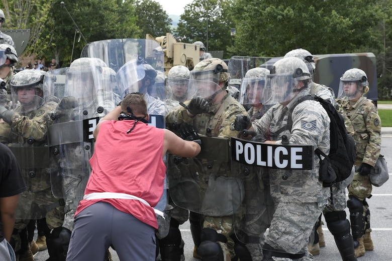 U.S. Air Force Tech. Sgt. Shane Johnson (right) holds back mock protestors at a simulated riot for Vigilant Catamount at Western Carolina University, Cullowhee North Carolina, June 13, 2017. Vigilant Catamount is a mulitday, multi-agency training exercise ending with simulated riot at Western Carolina University, involving Army National Guard Military police and the 145th Airlift Wing Security Forces.