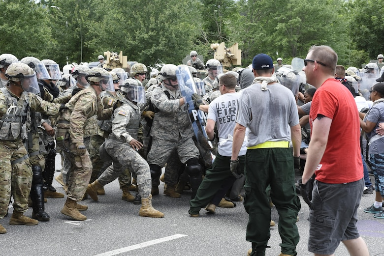 U.S. Air Force Tech. Sgt. Shane Johnson holds back mock protestors at a simulated riot for Vigilant Catamount at Western Carolina University, Cullowhee North Carolina, June 13, 2017. Vigilant Catamount is a mulitday, multi-agency training exercise ending with simulated riot at Western Carolina University, involving Army National Guard Military police and the 145th Airlift Wing Security Forces.