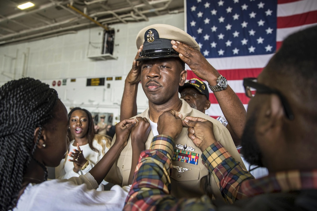 A sailor's family members participate in a ceremony promoting him to the rank of senior chief petty officer.