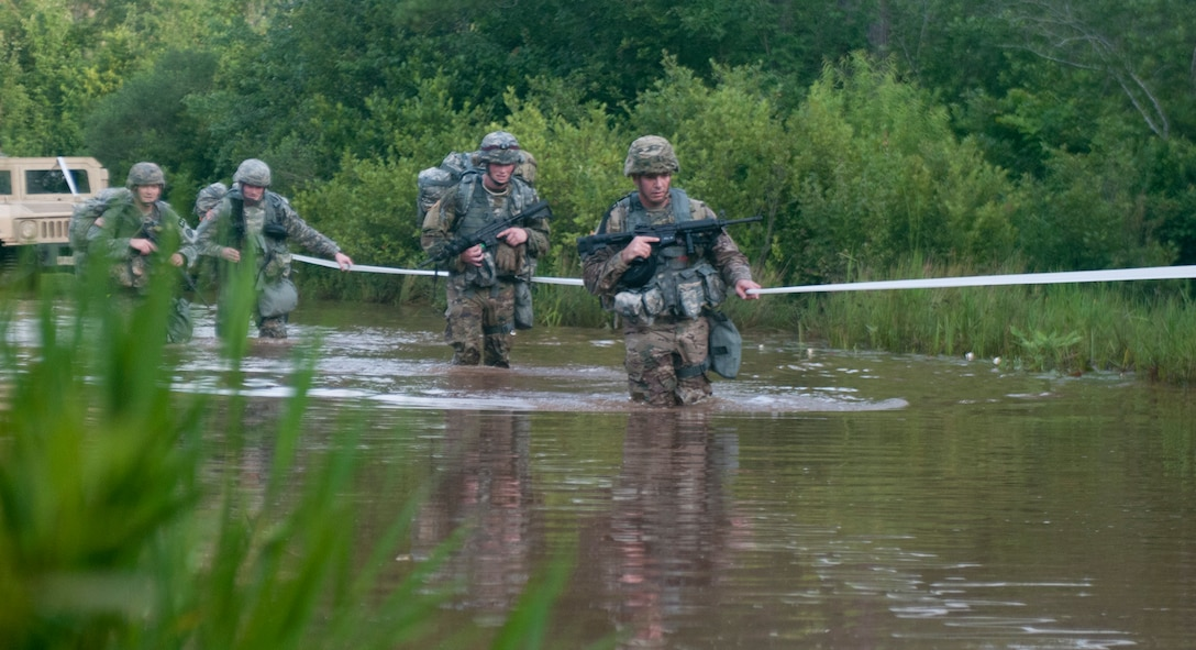 Warriors cross water during a 10-kelometer foot march at the 2017 U.S. Army Reserve Best Warrior Competition at Fort Bragg; N.C. June 13. This year's Best Warrior Competition will determine the top noncommissioned officer and junior enlisted Soldier who will represent the U.S. Army Reserve in the Department of the Army Best Warrior Competition later this year at Fort A.P. Hill; Va. (U.S. Army Reserve photo by Trenton Fouche) (Released)