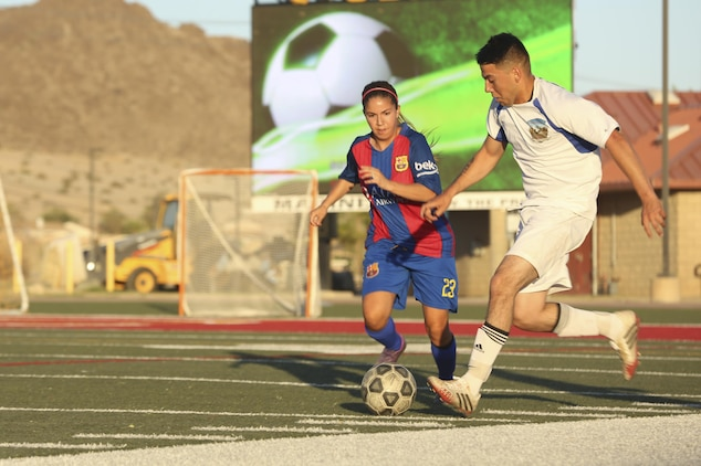 Miguel Torres, midfielder, Headquarters Battalion team, fights for possession of the ball against a marine from 1st Tank Battalion team during the intramural soccer championship game at Felix Field aboard the Marine Corps Air Ground Combat Center, Twentynine Palms, Calif., June 12, 2017. Marine Corps Community Services, Semper Fit, hosts an intramural soccer league for units aboard the installation. Tanks came out victorious with a score of 2-1. (U.S. Marine Corps photo by Lance Cpl. Christian Lopez)
