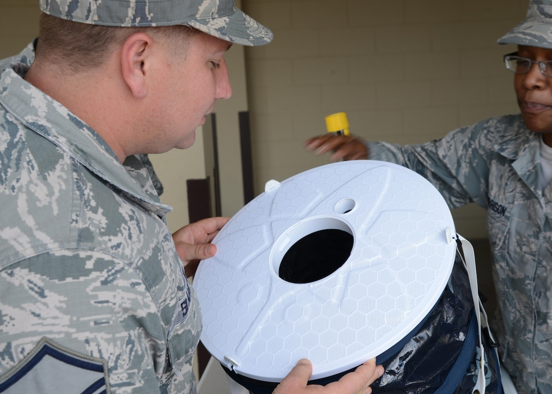 U.S. Air Force Master Sgt. Edward Slaughter, 47th Medical Group first sergeant (left), peers into a mosquito trap during the Healthy Lifestyle Festival at Laughlin Air Force Base, June 13, 2017. Public Health uses these traps to monitor the mosquito population on base, and the potential viruses carried by them. (U.S. Air Force photo/Airman 1st Class Benjamin N. Valmoja)