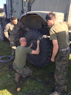 Marines of Service Company conduct field maintenance on a 7-ton during Battalion Exercise 1-2017.