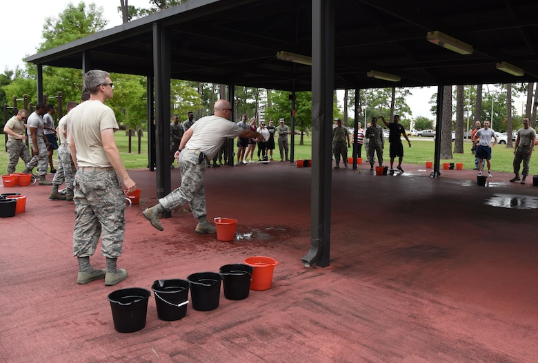 Keesler personnel participate in a bucket pong competition at the Crotwell Track June 12, 2017, on Keesler Air Force Base, Miss. The competition was one of several Wingman Week events focusing on resiliency and teambuilding initiatives across the base. (U.S. Air Force photo by Kemberly Groue)