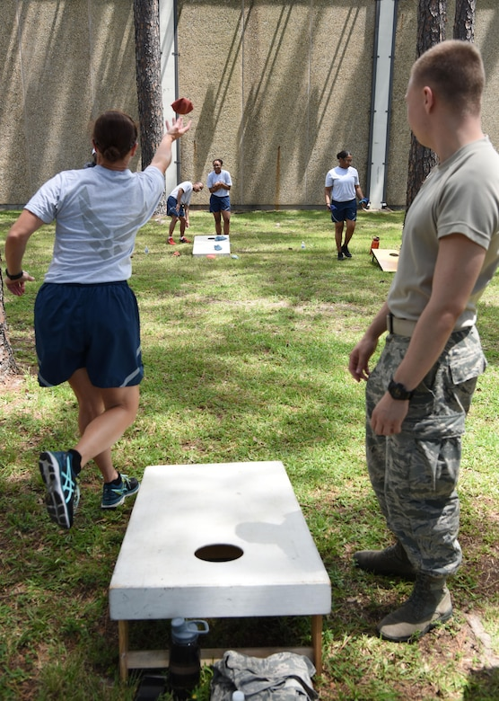 Keesler personnel participate in a cornhole competition behind the Blake Fitness Center June 13, 2017, on Keesler Air Force Base, Miss. The competition was one of several Wingman Week events focusing on resiliency and teambuilding initiatives across the base. (U.S. Air Force photo by Kemberly Groue)