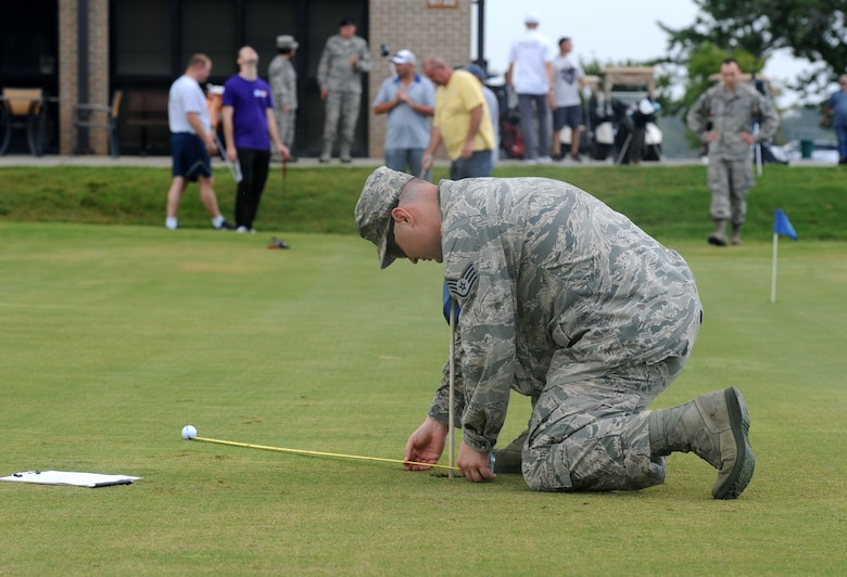Staff Sgt. Adam Pugh, 338th Training Squadron instructor, measures distance in a golf putting competition at the Bay Breeze Golf Course June 14, 2017, on Keesler Air Force Base, Miss. The competition was one of several Wingman Week events focusing on resiliency and teambuilding initiatives across the base. (U.S. Air Force photo by Kemberly Groue)