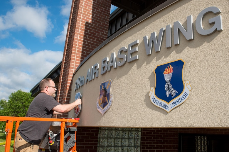 Michael J. Hafstad, a maintanence mechanic with the 319th Civil Engineering Squadron installs the Air Combat Command shield over the wing headquarters building June 14, 2017, on Grand Forks AFB, N.D.  The base underwent a realignment from the Air Mobility Command to Air Combat Command effective June 13, 2017. (U.S. Air Force photo by Master Sgt. Eric Amidon)