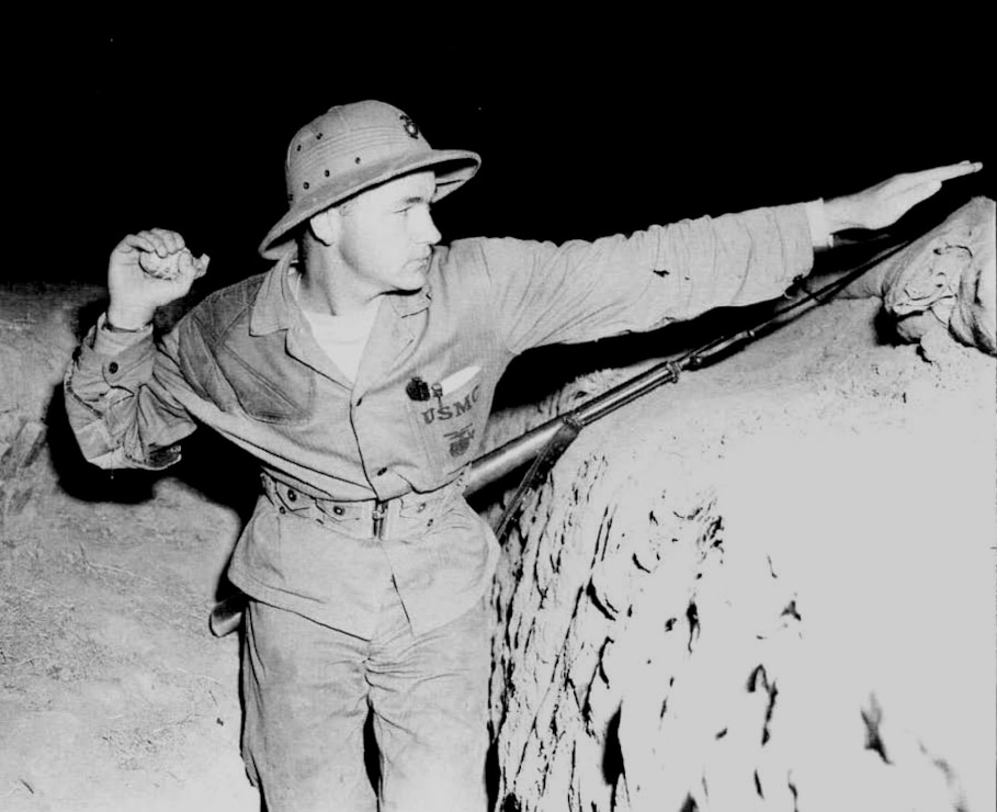 Marine private stands ready to throw a practice hand grenade from a trench at this Marine Corps Rifle Range where he is undergoing intensive recruit training. Camp Matthews, November 1945.